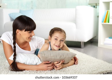 Portrait of happy girl and her mother resting at home
