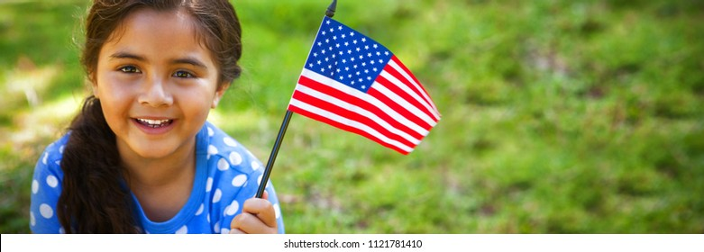 Portrait of happy girl holding American flag in park