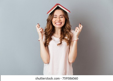 Portrait of a happy girl holding book on her head with crossed fingers for good luck isolated over gray wall background