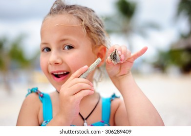 A portrait of a happy girl holding a hermit crab in her hand and pointing to it with a piece of coral