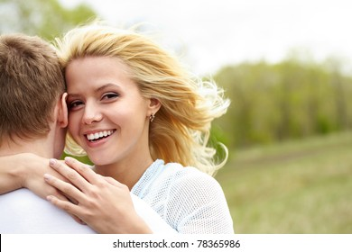 Portrait of happy girl hugging her boyfriend outside