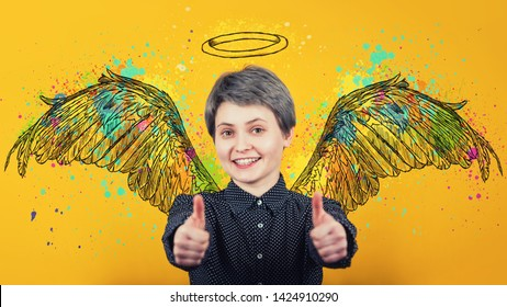 Portrait of happy girl keeps thumbs up over yellow background, smiling broadly imagining herself an angel with fluffy wings behind back and a halo above head. Super power, inner strength concept.