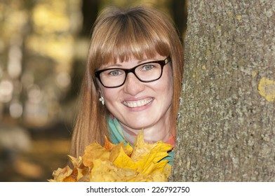 portrait of the happy girl with leaves near a tree trunk
