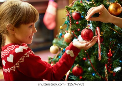 Portrait of happy girl looking at decorative toy ball by Christmas tree