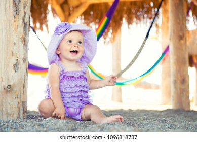 Portrait of happy girl on vacation. Against a background of hammocks, a little girl is sitting in a purple plait.