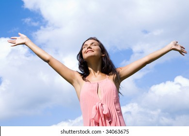 Portrait of happy girl praising God with her eyes shut and raised arms on background of cloudy sky
