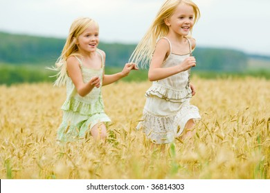 Portrait of happy girl running down wheat field with her twin sister behind