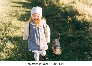 Portrait of a happy girl running through the field with a dog
