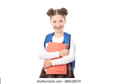 Portrait of happy girl in school uniform with backpack holding textbooks and pencils against white background
