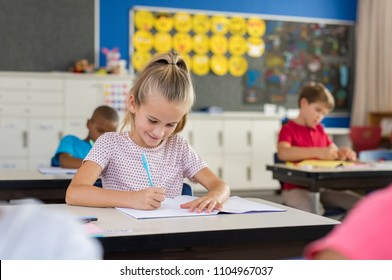 Portrait of happy girl sitting at school desk studying in classroom. Smiling schoolgirl doing classwork with classmates in background. Clever female student taking notes on notebook at primary school.