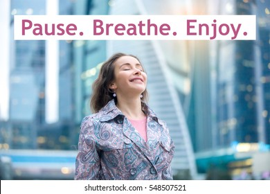 """Portrait of happy girl at street, her eyes closed with enjoyment, breathing at full outside. Lady feeling free, successful, ready to start day. Photo with motivational text """"Pause. Breathe. Enjoy."""""""