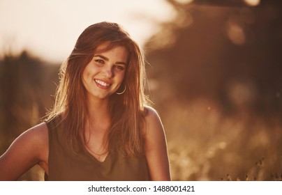 Portrait of happy girl that standing in the field illuminated by sunlight.