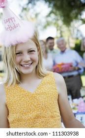 Portrait of happy girl wearing birthday cap