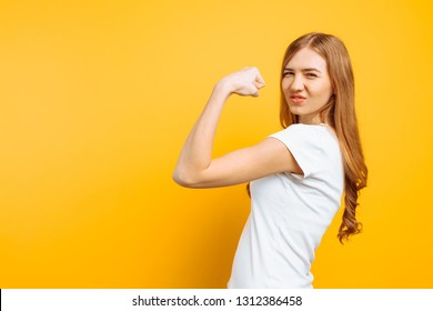Portrait of happy girl in white t-shirt showing arm muscles on yellow background.