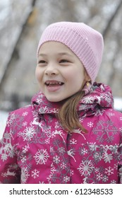 Portrait of the happy girl in winter clothes