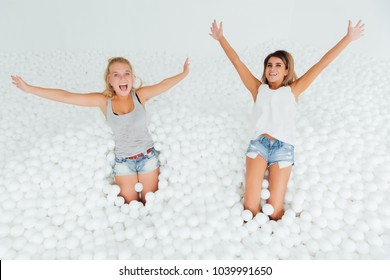 Portrait Happy Girlfriends stand surrounded by white plastic balls in the dry pool. Spend fun time. Adult childhood at Playground with pit-ball. Falling on the back.