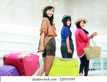 portrait of Happy girls going on vacation walking with suitcase and smile