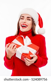 Portrait of happy glad woman in santa cap holding xmas present