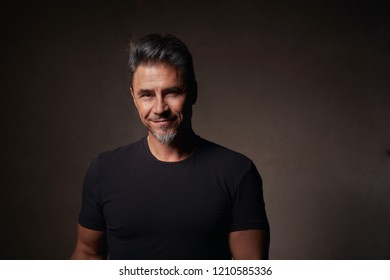 Portrait of a happy good looking older white guy against dark background.