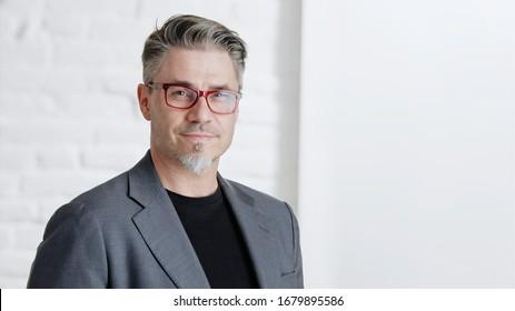 Portrait von glücklich gut aussehenden älteren Geschäftsmann in Brille mit Jacke, lächeln vor weißem Hintergrund mit Kopienraum..