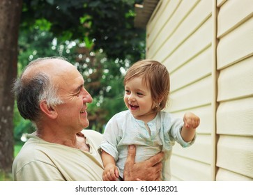 Portrait of Happy grandfather and granddaughter playing in the garden at Summer Day