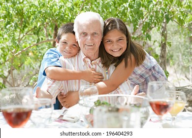 Portrait of a happy grandfather with his joyful grand children hugging him during a sunny summer day on a holiday home green garden while having lunch outdoors. Family relaxing on vacation, lifestyle.