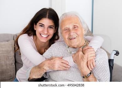 Portrait Of Happy Grandmother And Daughter Embracing Each Other At Home