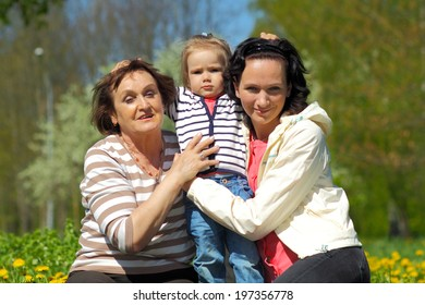Portrait of happy grandmother, daughter and granddaughter outdoors. Three generations of female. little girl funny hugging her mother and grandmother