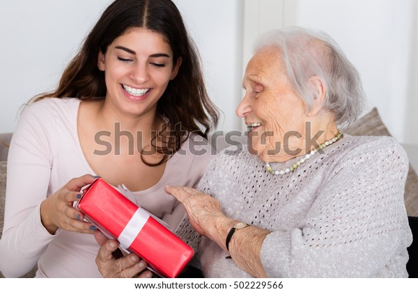 Portrait Of Happy Grandmother Giving Gift To Her Granddaughter At Home