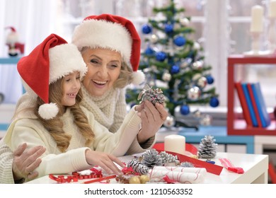 Portrait of happy grandmother and her little granddaughter preparing for Christmas