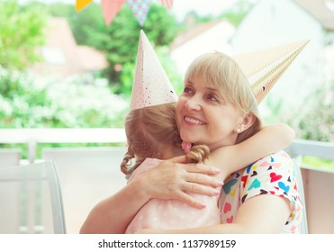 Portrait of happy grandmother hug her granddaughter at her birthday party on decorated terrace