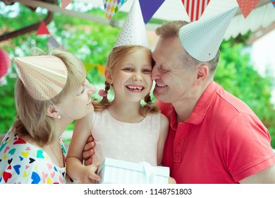 Portrait of happy grandparents celebrating birthday with their pretty little granddaughter on colorful decorated terrace