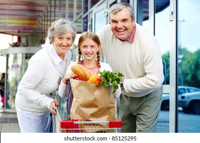 Portrait of happy grandparents and granddaughter near supermarket