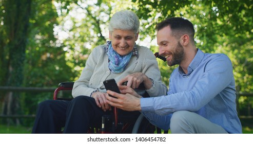 Portrait of  happy grandson and grandmother in a wheelchair are having fun to look their photos or navigating in internet in cellular phone in a green park on a sunny day.
