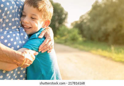 Portrait of happy grandson hugging grandmother over a nature outdoor background