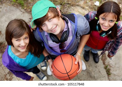 Portrait of happy guy and girls looking at camera in the park