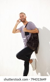 Portrait of happy guy leaning against wall talking on mobile phone