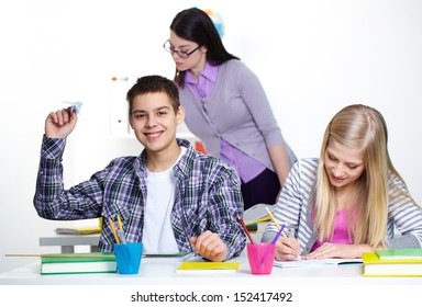 Portrait of happy guy playing with paper plane at lesson