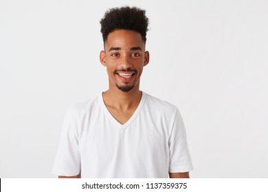 Portrait of happy handsome african american young man with afro hairstyle wears t shirt looks confident and smiling isolated over white background Looks directly in camera