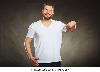 Portrait of happy handsome fashionable casual man in white blank shirt with empty copy space pointing at himself. Young guy in studio on black. Fashion advertisement.