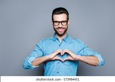 Portrait of happy handsome man in glasses making heart with fingers.