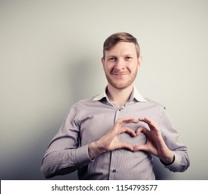 Portrait of happy handsome man making heart with fingers.