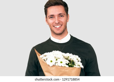 Portrait of happy handsome man smiling giving a bouquet of white flowers. Attractive male model with a bunch of flowers preparing for a date with girlfriend. Valentine's Day. Mother's Day concept