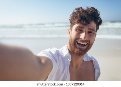 Portrait of happy handsome young Caucasian man taking a selfie standing and at beach on sunny day. He is smiling and looking at camera
