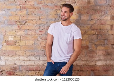Portrait of a happy handsome young man in a white tshirt.