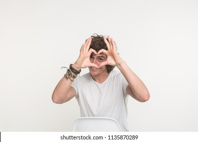 Portrait of happy handsome young man making heart with fingers on white background