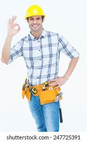 Portrait of happy handyman gesturing OK sign over white background