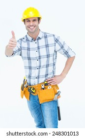 Portrait of happy handyman gesturing thumbs up sign over white background