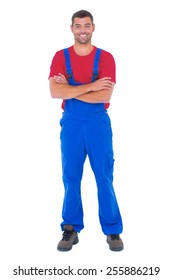 Portrait of happy handyman in overalls standing arms crossed over white backgound