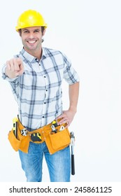 Portrait of happy handyman pointing over white background